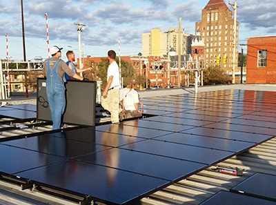 Workers installing solar panels on Kingfisher Rooftop in Kinston