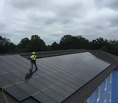 Worker installing solar panels on roof of Mayton Inn in Cary NC.