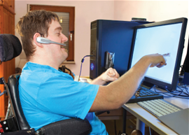 Photo of a person using a computer with assistive technology