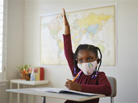 Masked child raising hand in a classroom