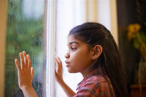 Girl stares at rain through window