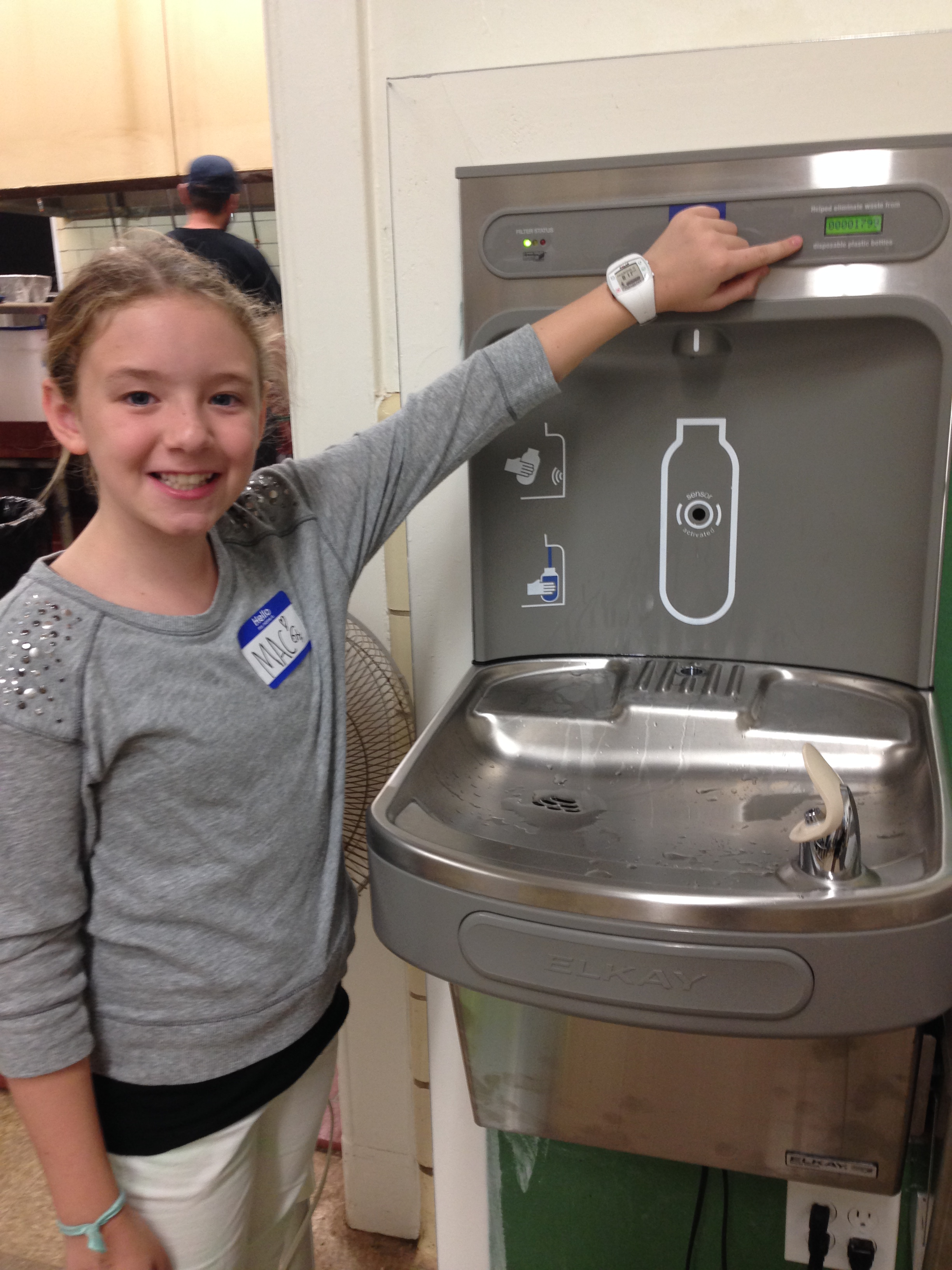 A student points out the amount of waste reduced thanks to the water-bottle filling station.